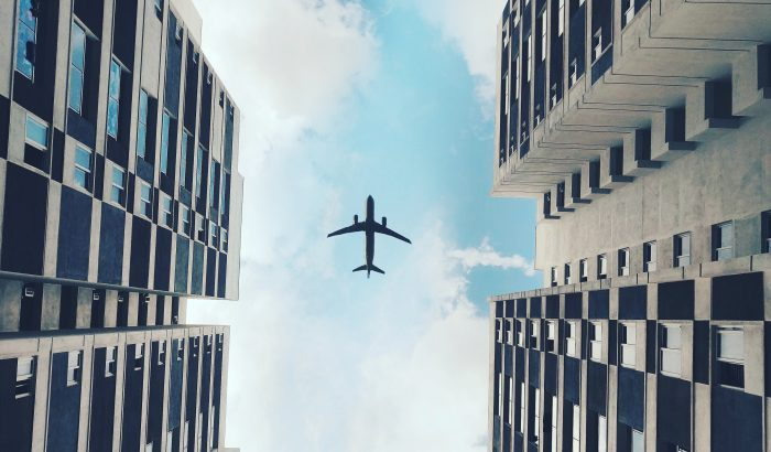 Photo of airplane above flying in between two buildings, photo from Pexels by Salih Sayed